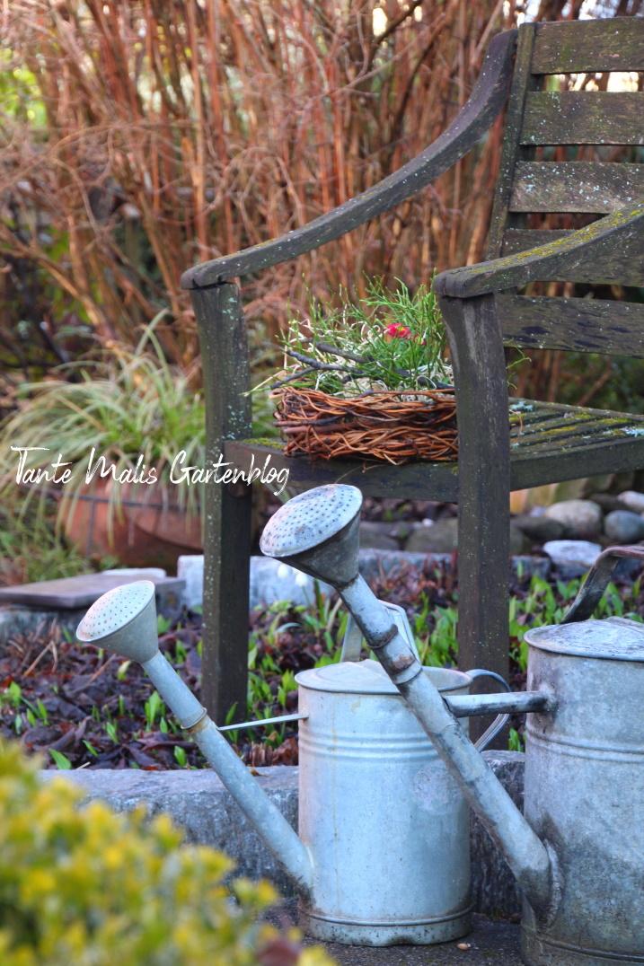 Zinkkannen und Stuhl als Gartendeko
