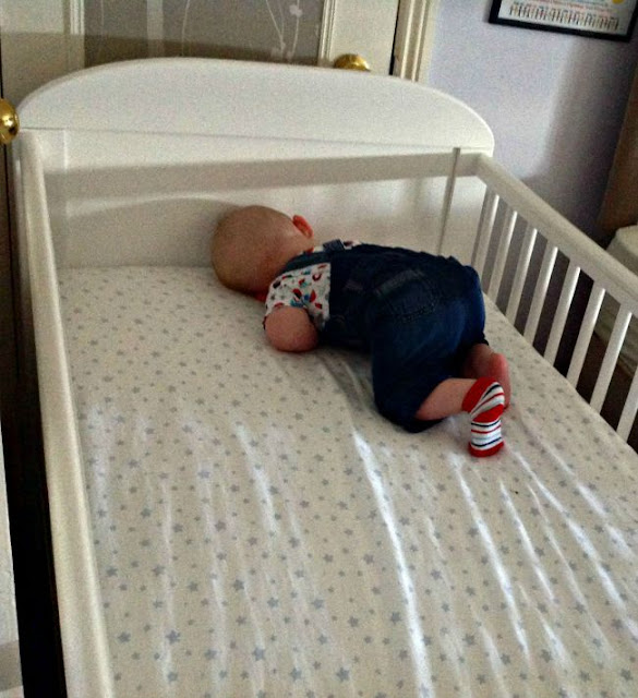 baby asleep in corner of large white cot