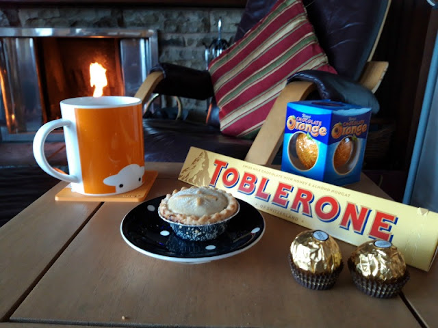 A photo of a small table with an orange mug with a Herdy log, a Terry's Chocolate Orange, a Toblerone, a mince pie on a black and white spotted saucer and two Ferrero Rocher chocolates on it.  In the background is a brown leather rocking chair and an open fire in a chrome fireplace