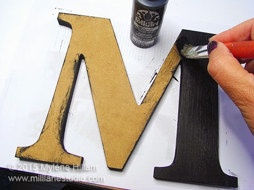 "Applying the first coat of Folk Art Licorice acrylic paint to the wooden ""M"" with a stiff paintbrush"