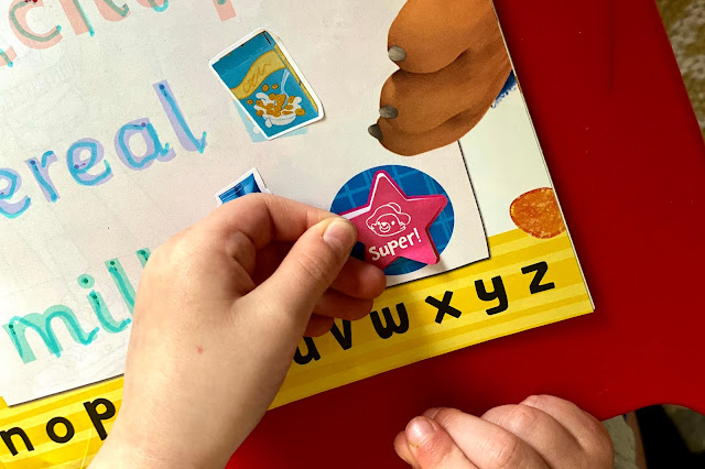 Close up of a child sticking on a star shaped super sticker to the adventures of paddington magazine