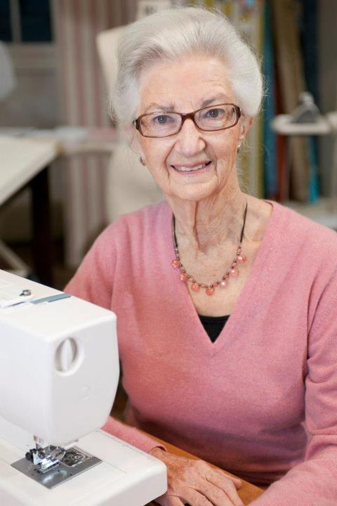Older woman in a pink sweater sitting at a sewing machine and looking straight at the camera