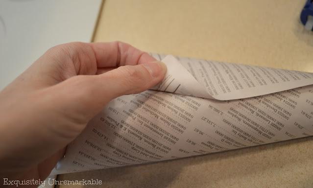 A hand folding newspaper into a cone