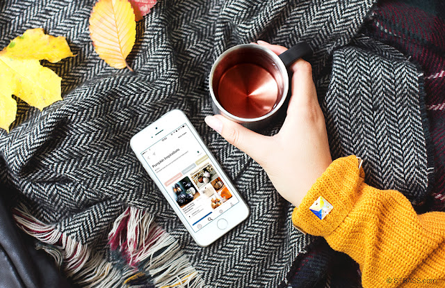 This picture shows an autumnal flatlay with a scarf, a mug of tea and a mobile phone showing our Pinterest board for pumpkin decorations.