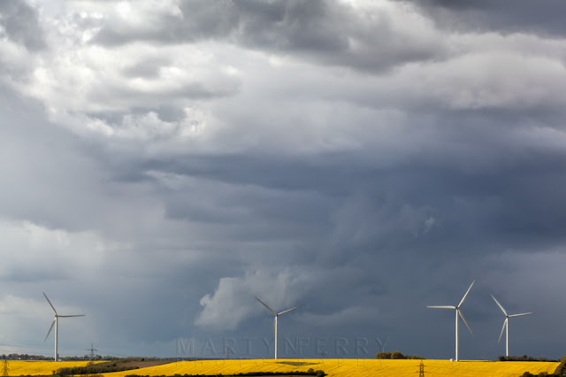 Dramatic landscape of wind turbines in a yellow field under a sky full of storm clouds