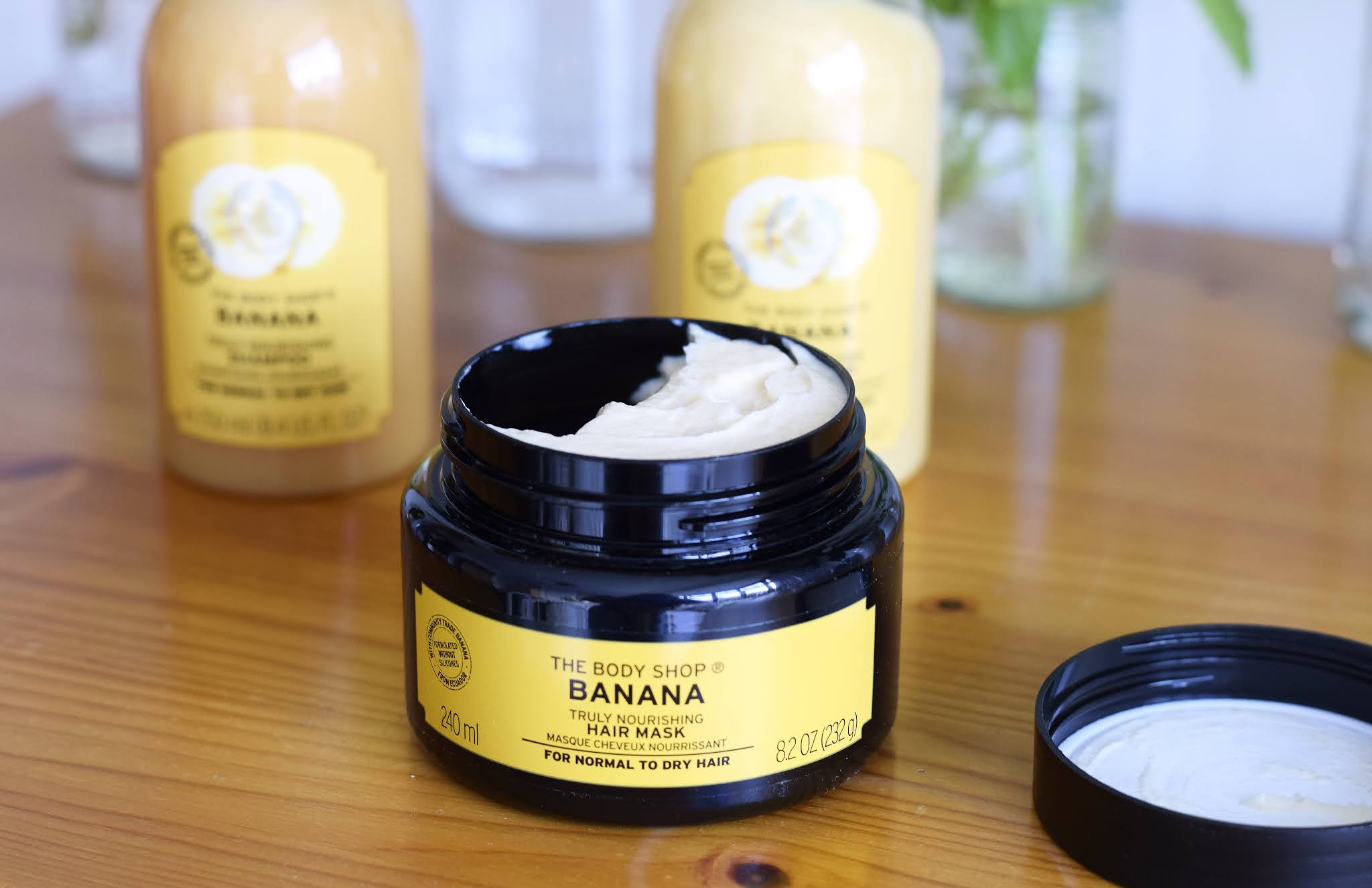 a pot of banana hair mask with the lid off. the creamy product can be seen inside.