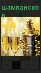 стоят два бокала и бутылка шампанского в ведерке находится