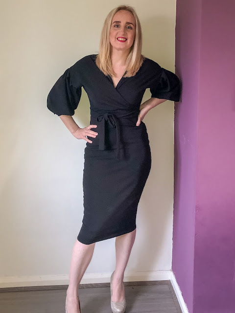 Standing in a black 3/4 length slinky midi dress / winter dresses from Femme Luxe