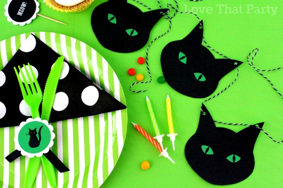 image of kids halloween party table setting with cat garland bunting