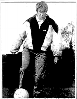 Short-haired woman wearing a shell suit and kicking a football