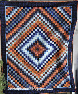 A single-bed sized Trip Around the World quilt in oranges and blues.