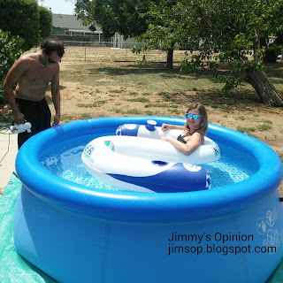 Daughters fiance adding air to a small pool with Daughter Melissa floating inside the water on a pool noodle
