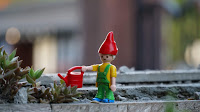 A Lego-man toy with a red watering can in a planter.