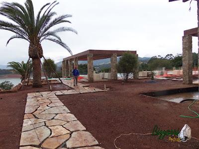 Execução do caminho no jardim com pedra Goiás tipo cacão com execução do revestimento de pedra nos pilares do pergolado de madeira com o início do paisagismo fazendo o acerto de terra na residência em Piracaia-SP.