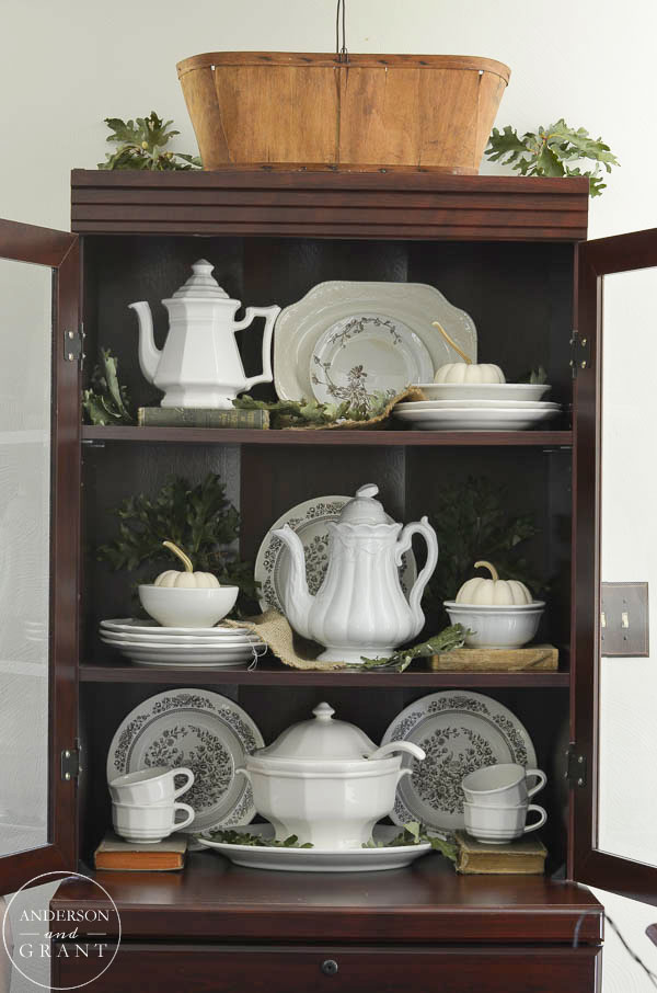 Fill open shelves with a collection of ironstone and pumpkins and leaves for a simple fall display.  |  www.andersonandgrant.com
