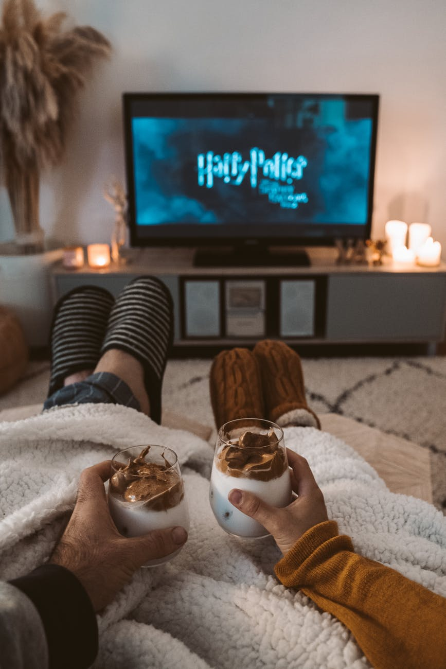 couple sitting watching Harry Potter, holding coffee