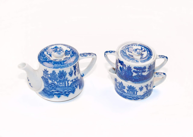 A small 1-cup tea pot and stacking cream and sugar with a blue willow pattern.