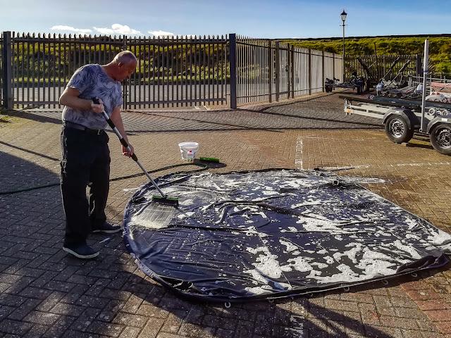 Photo of Phil scrubbing Ravensdale's flybridge cover