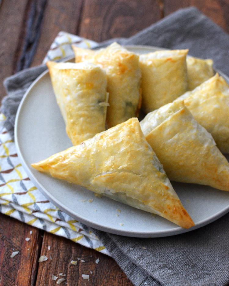 Pastelitos o triángulos de masa filo con relleno de acelgas, tocineta y queso suizo