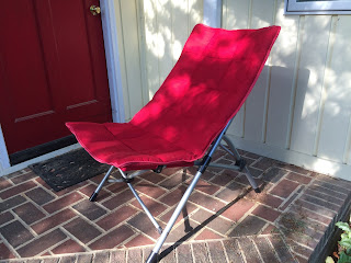 Red upholstered folding chair.