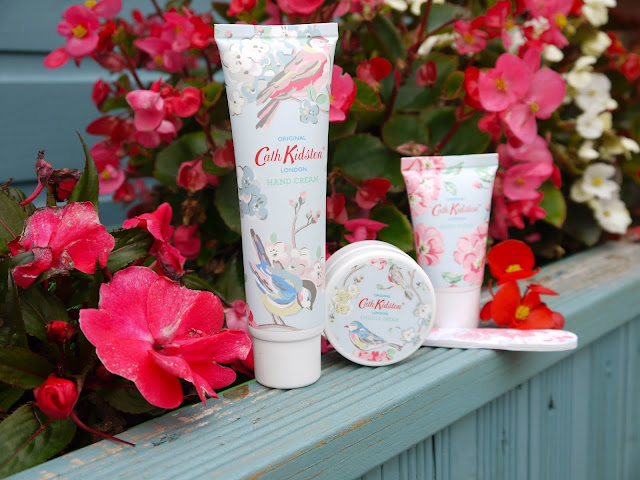 2 tubes, a tub, and a nail file all printed with pastel flowers and birds stand on a blue wooden ledge with pink and red flowers behind them