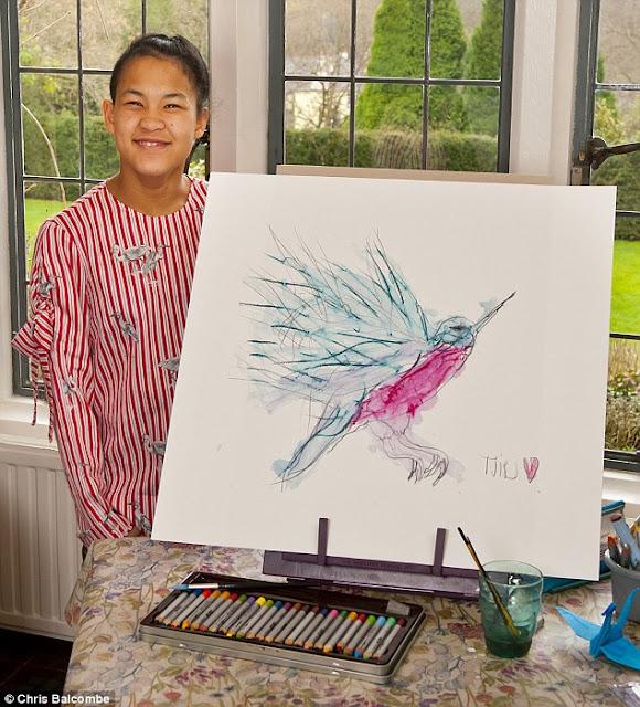 Tjili, sorda y con parálisis cerebral, posando con una de sus obras, un colibrí
