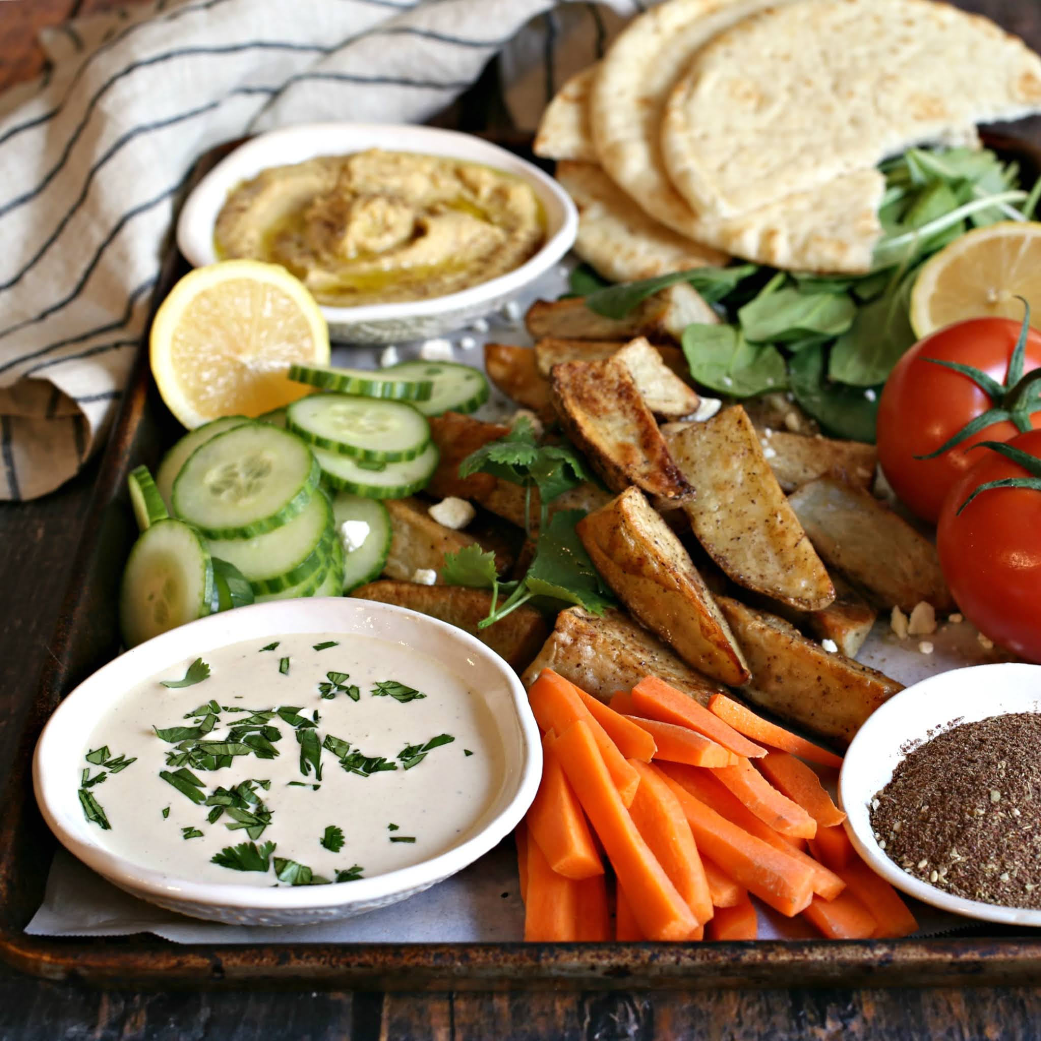 Recipe for a Middle Eastern inspired appetizer platter with za'atar roasted potatoes, hummus and tahini dips.