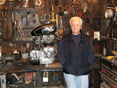 Man standing against work bench in motorcycle shop.