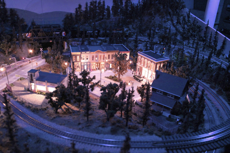 HO scale model railroad layout downtown scene at night with accessory lighting effects