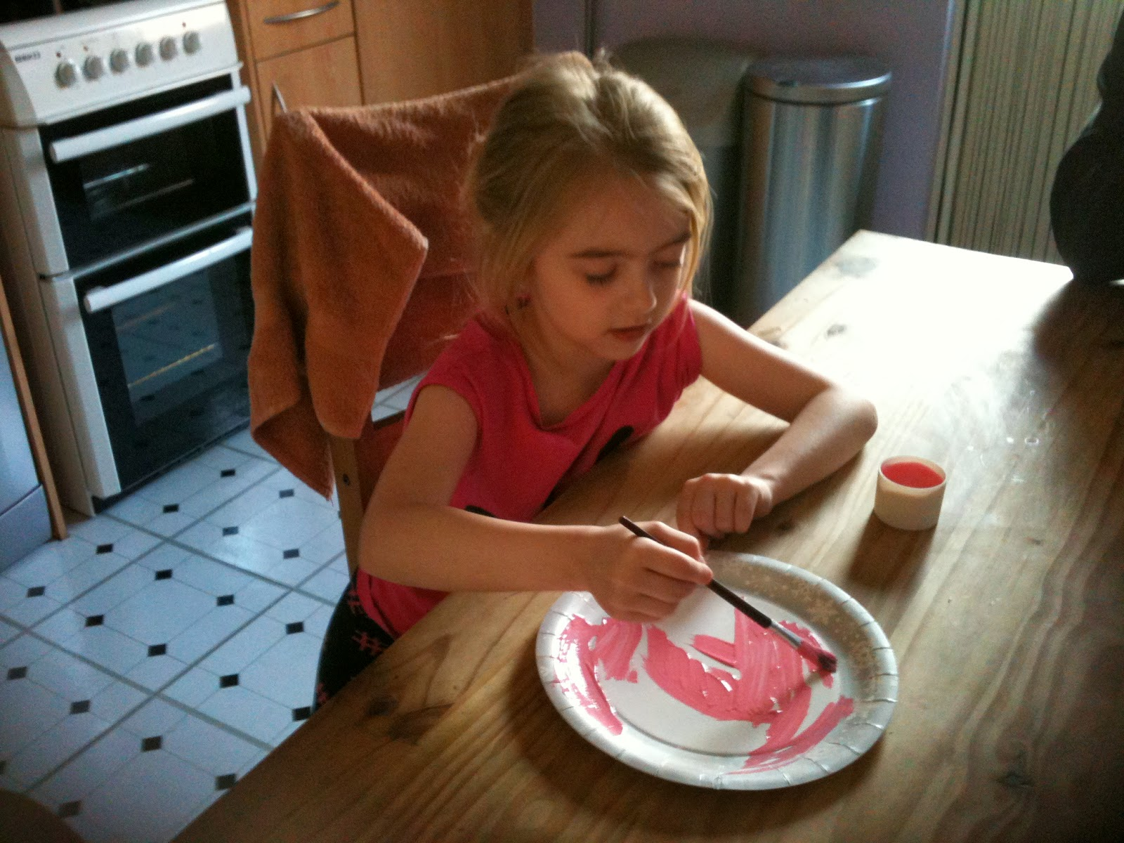 Girl painting a paper plate pink