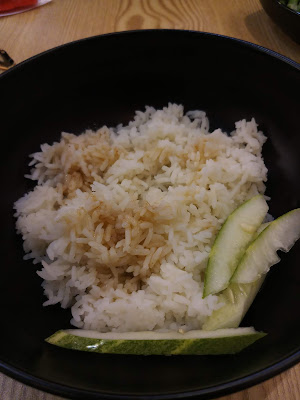 Rice flavoured with soya sauce and topped with some slices of cucumber