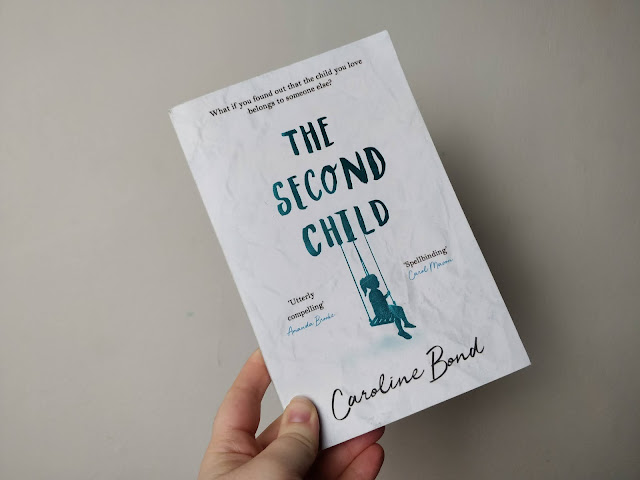 "A fair skinned hand is holding up a book against a cream coloured background. The book has a white crumpled paper texture cover with The Second Child written in foiled blue text. An image of a girls silouette on a swing hangs from the letters in child. The bottom reads Caroline Bond in black script text. The right side has small text saying "" Utterly Compelling"" Amanda Brooke. The right side also has text saying "" Spellbounding"" Carol Mason."