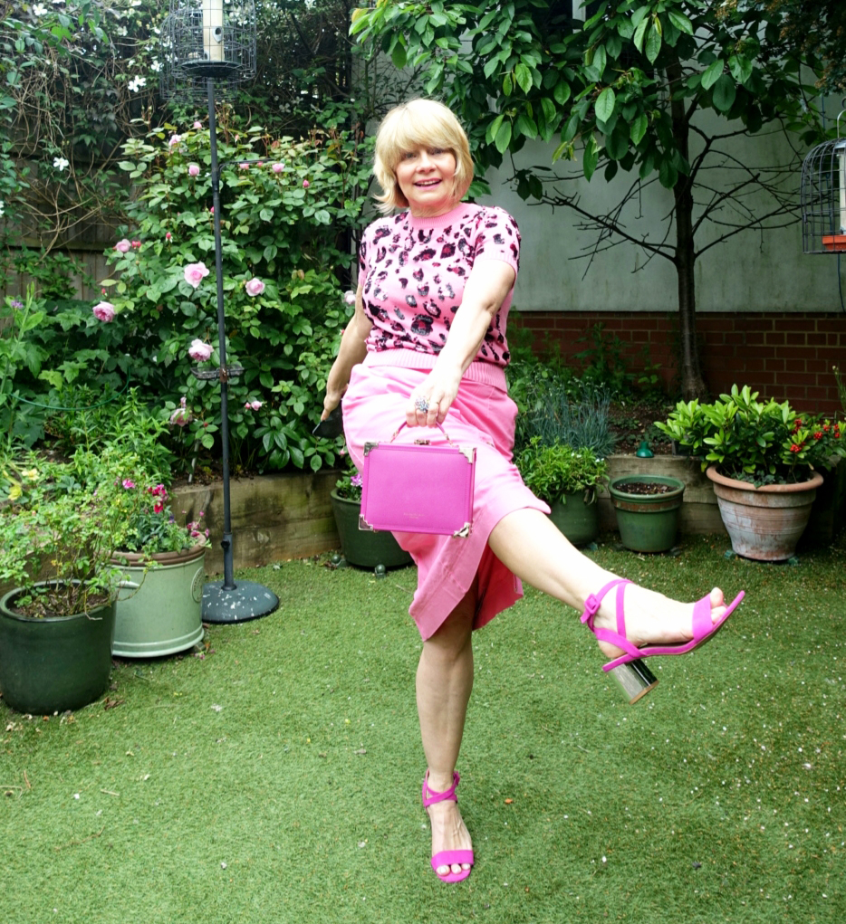 Midlife woman in garden wearing pink midi skirt and pink animal print jumper and carrying a small pink trunk bag