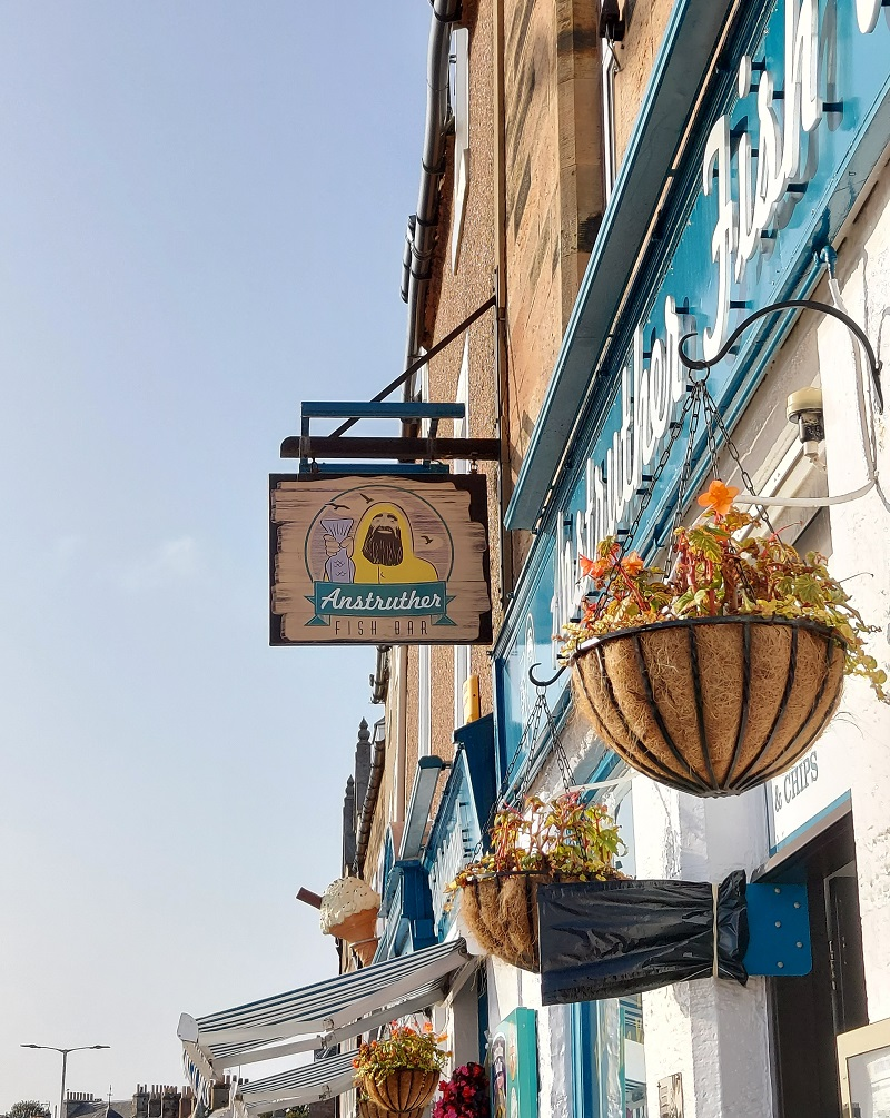 Anstruther fish bar facade with striped awning, hanging baskets & fisherman sign