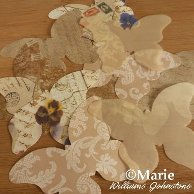 Butterfly shapes cut out from patterned scrapbook and vellum papers