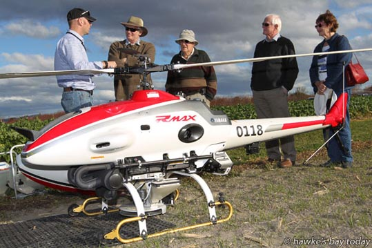 L-R: Greg Quinn, UAV operator, Yamaha Motor New Zealand Ltd, Auckland, demonstrating a Yamaha RMAX G II agricultural UAV Unmanned Aerial Vehicle to Philip Alexander, Puketapu, Jasper Nowell-Usticke, Napier, Roger Alexander, Puketapu, Ruth Nowell-Usticke, Napier, photograph