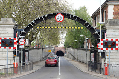 Photograph of a tunnel entrance. In the foreground is a metal arch between stone posts, with a height restriction sign on the top and a black-and-yellow horizontal bar. There are warning lights to either side, and a raised barrier. Round traffic signs indicate no overtaking for 1.25 miles. Beyond the arch are two cars driving along a narrow two-lane road towards the arched mouth of a tunnel whose interior appears dark. The approach is lined with trees and a brick building.
