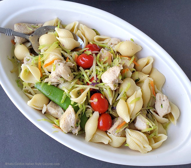 this is a delicious pasta salad made with shell pasta and vegetables in a salad style dressing in a white dish