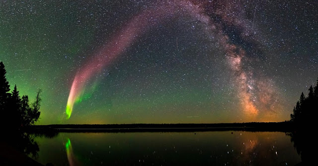 The Strong Thermal Emission Velocity Enhancement, visible as a pink band rising from the lower left to upper right of this photograph, appears with the Milky Way over Childs Lake, Manitoba, Canada. Scientists have recently confirmed STEVE is a unique phenomenon and not a kind of aurora, as previously thought. The picture is a composite of 11 images stitched together. Image courtesy of Krista Trinder and NASA
