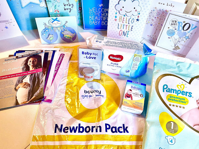 A flat lay of the contents of the Bounty Newborn pack with lots of new baby welcome cards in the background