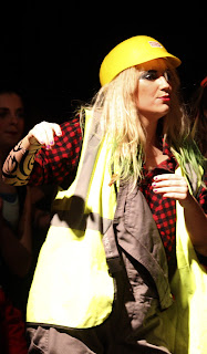 Picture of girl bohemian cast member wearing yellow builders hat and jacket