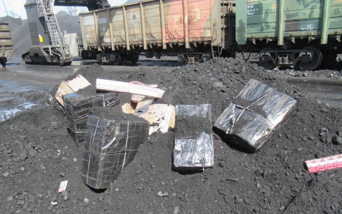 Cigarešu paciņas, ietītas polietilēna maisos guļ uz oglēm
