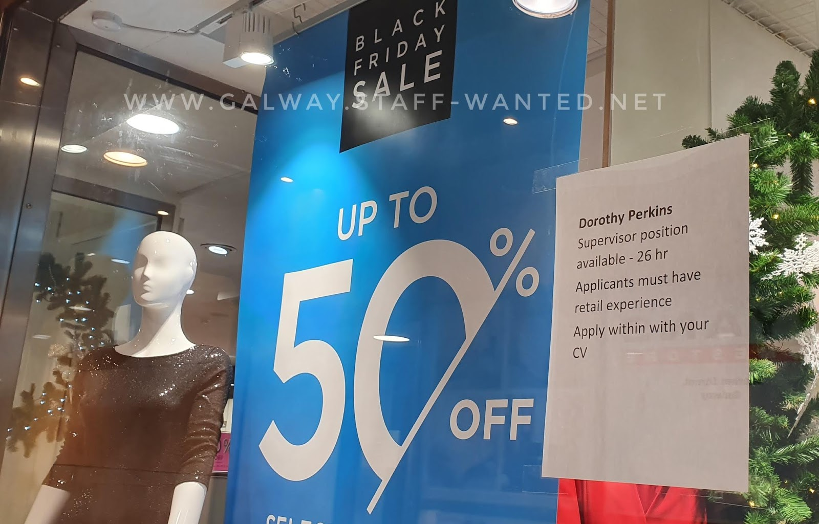 shop window with a job advertisement and two mannaquins (in a black and a red dress) and a Black Friday 50% off sign, with the zer on 50 being half-cut-off with part of a percentage discount sign