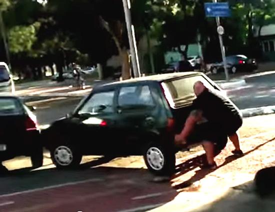 Homem levanta carro que estava no meio da ciclovia