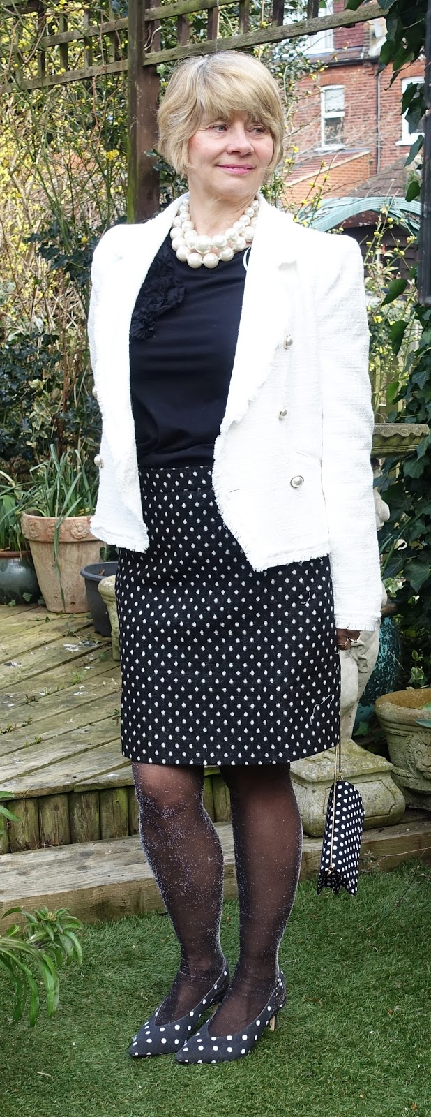 Image showing a woman wearing a white boucle jacket for spring with polka dot skirt and sling back shoes.