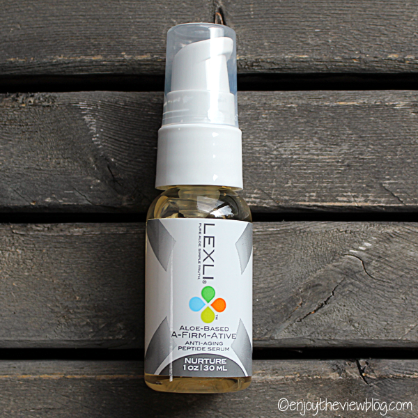 A bottle of Lexli A-Firm-Ative Anti-Aging Peptide Serum lying on a wooden table