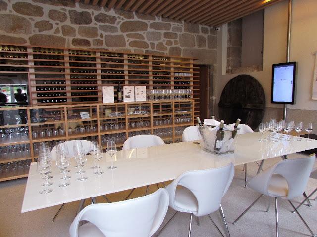 mesa com cadeiras, copos e garrafas ao redor , no Centro interpretativo do Vinho Verde