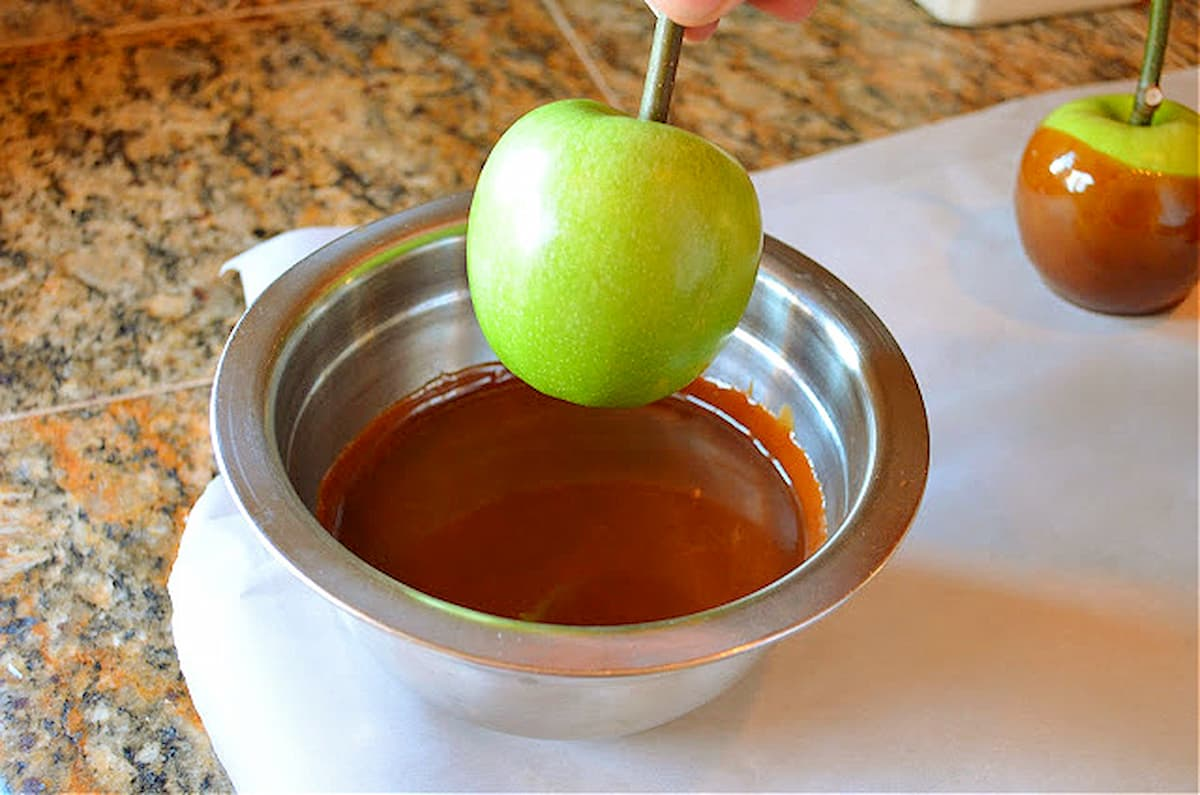 Granny Smith Apple about to be dipped into a stainless steel bowl full of caramel.