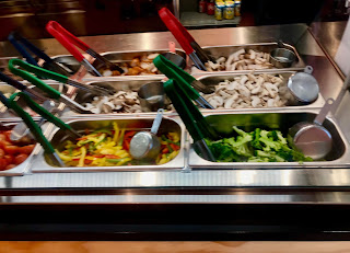Four rectangular metal trays next to each other in a square shape full of different coloured salad items with black large spoons on a bright background