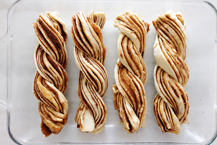 all four dough logs twisted and resting in baking pan